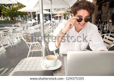 Close up portrait of a young businessman smiling and holding up his shades while using a laptop computer, sitting outdoors at a coffee shop terrace table.