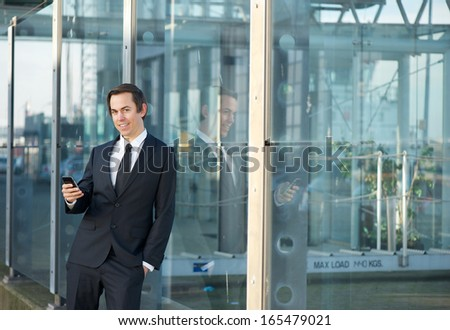 Close up portrait of a young businessman standing outdoors with mobile phone - stock photo
