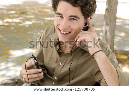 Close up portrait of a young businessman using his smart phone and hands free set to have a conversation while sitting on a bench, smiling.