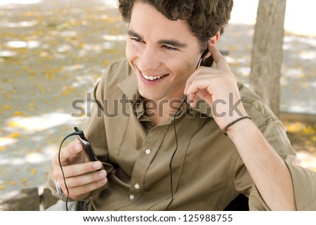 Close up portrait of a young businessman using his smart phone and hands free set while sitting under a tree, smiling. - stock photo