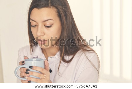 Close up portrait of a young businesswoman holding a cup of coffee and looking at it. - stock photo
