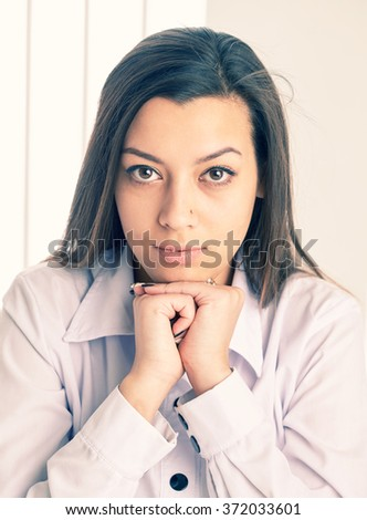 Close up portrait of a young businesswoman sitting with her chin on her hands. - stock photo