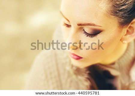Close up portrait of a young Caucasian girl. Golden color scheme. Soft fous, selective focus, shallow depth of field, shallow dof. - stock photo