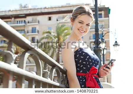 Close up portrait of a young fashionable woman holding and using a smartphone while standing in a city bridge with railings, buildings and street lamps during a sunny day in the summer. - stock photo