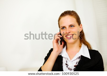 Close up portrait of a young friendly businesswoman on mobile phone and smiling - stock photo