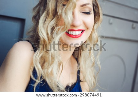 close-up portrait of a young girl hipster beautiful blonde  with red lips laughing and posing against the backdrop of the city - stock photo