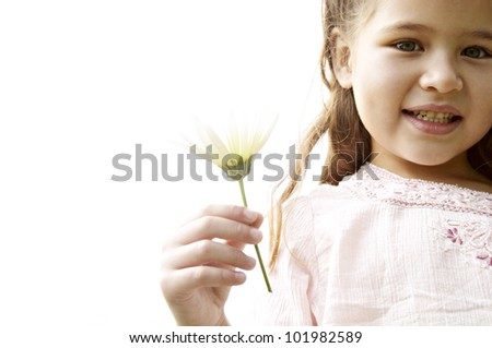 Close up portrait of a young girl holding a daisy flower in her hand, against the sky. - stock photo