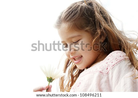 Close up portrait of a young girl holding a white daisy flower in her hand against the sky, smiling. - stock photo