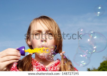 Close up portrait of a young girl in a park during the autumn season, wearing a red jumper and playing at blowing soap bubbles against a blue sky during a sunny winter day.