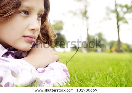 Close up portrait of a young girl laying down on green grass in the park, looking ahead. - stock photo