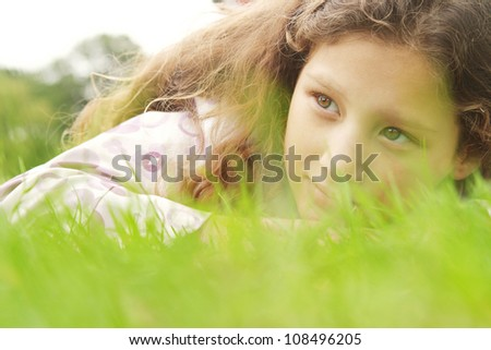 Close up portrait of a young girl laying on long green grass in the park, being thoughtful. - stock photo