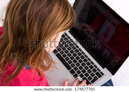Close up portrait of a young girl looking at laptop screen - from behind - stock photo