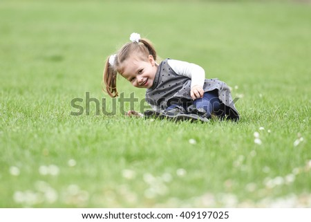 close up portrait of a young girl lying in the green grass in a field with flowers near her, smiling, showing teeth and looking happy on a sunny spring day - stock photo