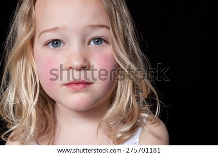 Close up portrait of a young girl on black background. - stock photo
