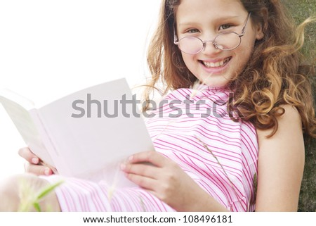 Close up portrait of a young girl reading a book in the park, smiling and looking at camera while leaning on a tree trunk. - stock photo
