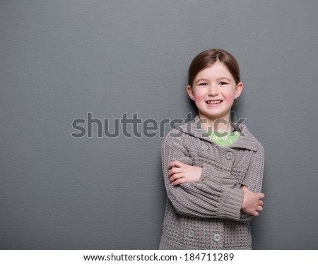 Close up portrait of a young girl smiling with arms crossed on gray background - stock photo