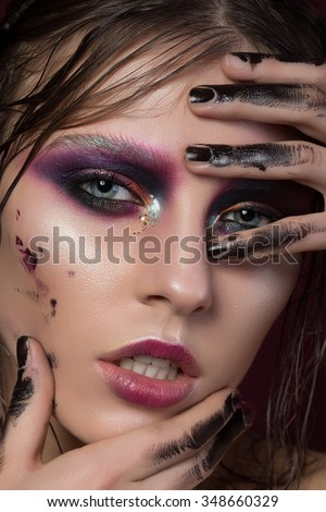 Close up portrait of a young girl with fashion creative make-up touching her face. Colourful smoky eyes. Modern make up