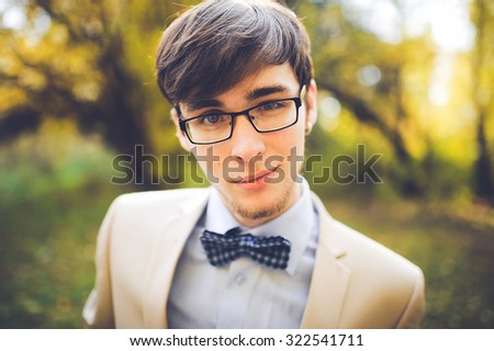 close-up portrait of a young handsome guy groom delectable hipster in a suit and bow tie on a background autumn forest smiling and posing with glasses - stock photo