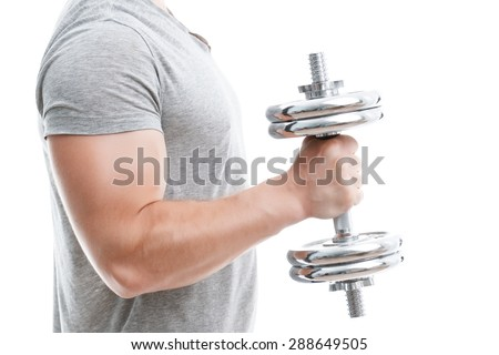 Close up portrait of a young handsome man wearing grey t-shirt standing and holding a silver dumbbell in his hand showing his muscled biceps during training, isolated on white background - stock photo