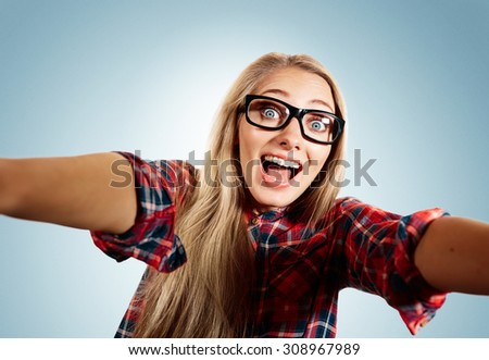 Close up portrait of a young joyful and cheerful blonde girl holding a smartphone digital camera with her hands and taking a selfie self portrait of herself standing against blue background