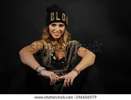 close up portrait of a Young latin girl wearing black and Golden vest and black hat with a word blog written on it seating with her hands on her knees on a black background - stock photo