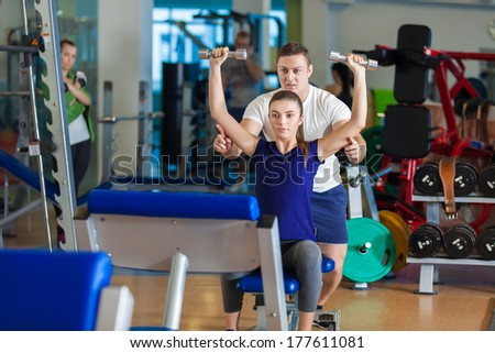 Close-up portrait of a young male gym instructor helping an young woman - stock photo