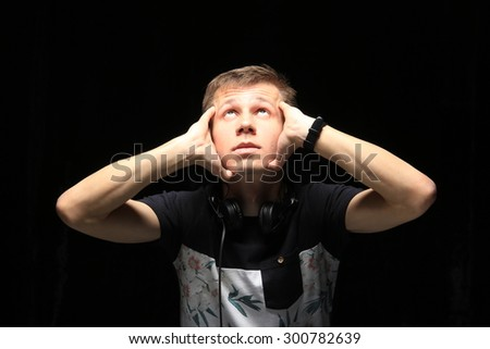 close-up portrait of a young man DJ with headphones on dark background studio - stock photo