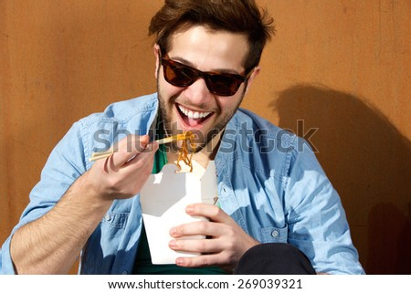 Close up portrait of a young man laughing and eating noodles with chopsticks - stock photo