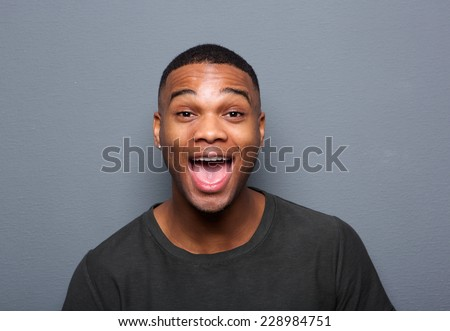 Close up portrait of a young man making funny face on gray background - stock photo