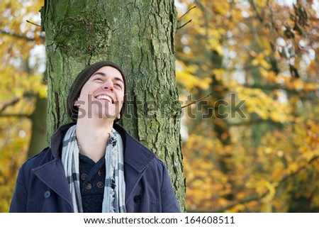 Close up portrait of a young man smiling outdoors - stock photo