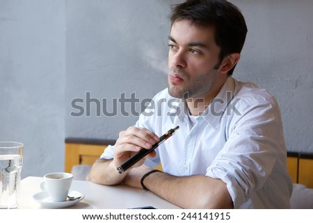 Close up portrait of a young man smoking e cigarette indoors