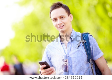 Close up portrait of a young man with phone and backpack
