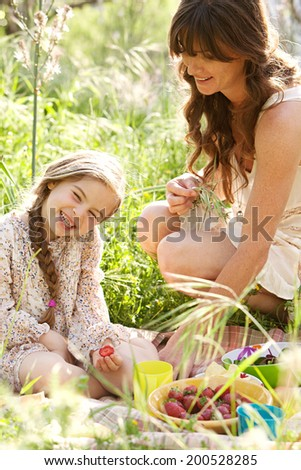 Close up portrait of a young mother and daughter relaxing together having a picnic in a green garden eating healthy food, laughing having fun. Family activities and healthy eating lifestyle, outdoors. - stock photo