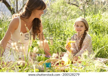 Close up portrait of a young mother and daughter relaxing together having a picnic in a lush green garden eating a healthy fresh banana. Family activities and healthy eating lifestyle, outdoors. - stock photo