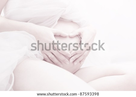 close-up portrait of a young pregnant woman making heart shape sign on her tummy - stock photo