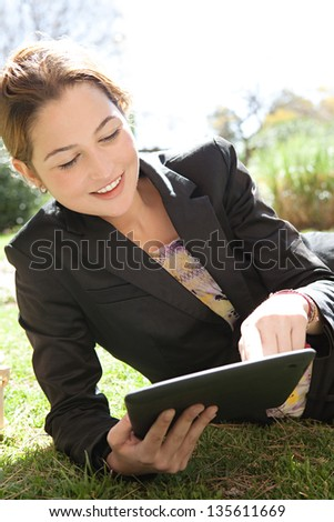 Close up portrait of a young professional woman laying down on green grass in a city park, using her digital tablet pad with touch screen, smiling. - stock photo