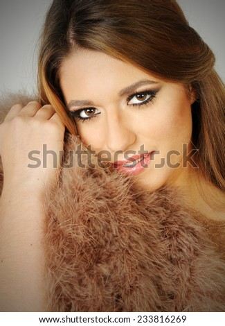 close up portrait of a Young sensual beautiful smiling girl posing leaning towards beige fur coat close to her face with perfect make up - stock photo