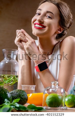 Close-up portrait of a young smiling sport woman with smart watch and healthy food on the foreground