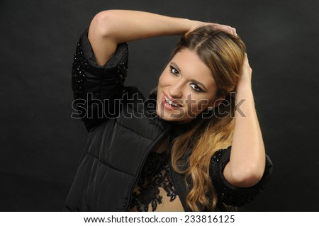 close up portrait of a Young smiling teenage model posing on the black background with her hands up wearing a lace silk negligee dress and black jacket  - stock photo