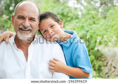Close up portrait of a young son and his grandfather relaxing and hugging in a green garden during a sunny day, enjoying each others company and smiling joyfully. Outdoors active lifestyle.