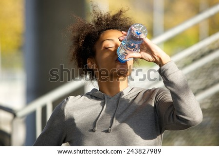 Close up portrait of a young sports woman drinking water from bottle - stock photo
