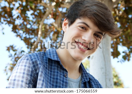 Close up portrait of a young student teenager boy near a tree, smiling joyfully at the camera during a sunny day out. Outdoors lifestyle. - stock photo