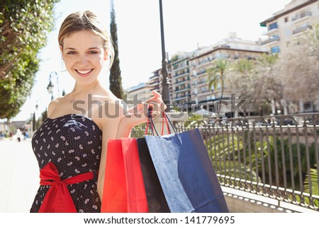 Close up portrait of a young stylish woman smiling at the camera while visiting a destination city on vacation and carrying red shopping bags over her shoulder during a summer day. - stock photo