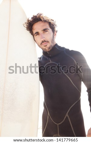 Close up portrait of a young surfer standing on a beach during a golden sunny day, holding his surfing board and looking at camera, being thoughtful. - stock photo