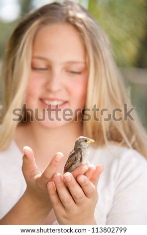 Close up portrait of a young teenage girl holding a baby bird in her hands, smiling. - stock photo