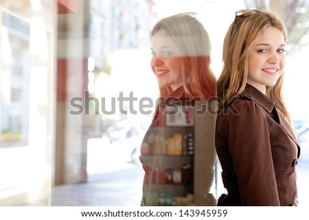 Close up portrait of a young teenager tourist visiting the city during the weekend and leaning on a shopping mall store window, turning to camera smiling and being joyful. - stock photo