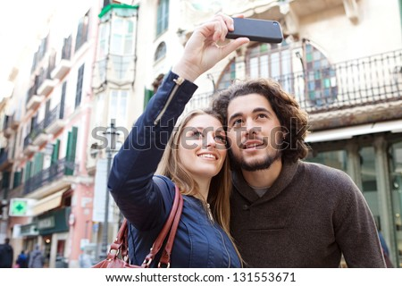 Close up portrait of a young tourist couple visiting a destination city and taking pictures of the classic buildings while on vacation in Europe. - stock photo