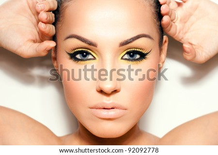 Close-up portrait of a young woman. Cat eyeliner makeup. - stock photo