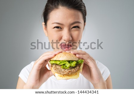 Close-up portrait of a young woman having an unhealthy yet yummy snack - stock photo