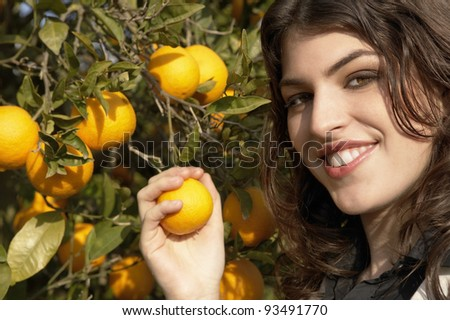 Close up portrait of a young woman holding an orange on a tree. - stock photo